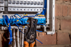 The Assembly of the electrical panel, electrician job, a robot with wires and circuit breakers Royalty Free Stock Photography