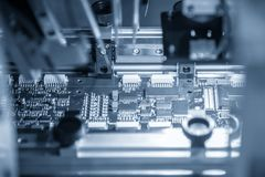 The assembly line of electronic board with microchip in the light blue scene.The electronics board production process. stock photography