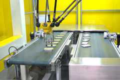Assembly line. Industrial robot arm on assembly line royalty free stock image