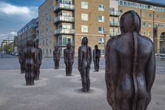 Group sculpture in the Woolwich Arsenal by Peter Burke. Assembly, by Peter Burke, Woolwich Arsenal, London. Statues standing in a group in an open space. Modern Royalty Free Stock Photo