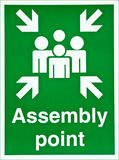Assembly point. Green fire sign with 2D graphics of people pointing arrows and the words assembly point Royalty Free Stock Photos