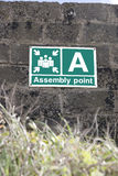 An assembly point sign. On a block wall in Ireland Stock Images