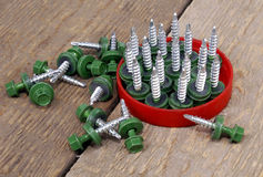 Assembly screws. Metal assembly screws lay on wooden boards Stock Photo
