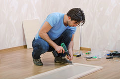 Assembly to furniture. Young man collects new furniture Royalty Free Stock Photography