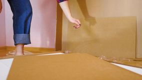 Assembly of white bedroom furniture, girl collects wood furniture in the house. Moving to a new apartment concept. stock footage