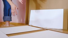 Assembly of white bedroom furniture, girl collects wood furniture in the flat. Moving to a new apartment concept. stock footage