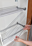 Assembly wire dish rack for drying dishes inside kitchen cabinet Stock Image