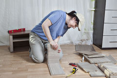 Assembly wooden furniture, woman glues part of drawer, on floor. Stock Photos