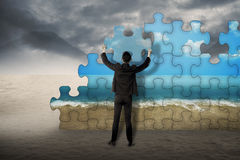 Assemle Puzzle To Change Desert To Sea Shore. Business man holding puzzle to assembly change situation from desert to sea shore Stock Photos