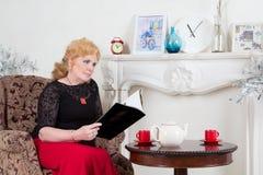 Assentado em uma mulher adulta da cadeira que lê um compartimento fotografia de stock royalty free