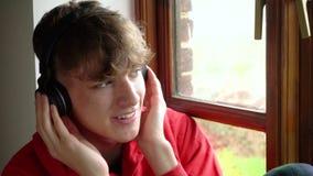 Assento adolescente masculino do homem novo do adolescente por uma janela que escuta a música em fones de ouvido e no telefone ce filme