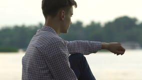 Assento adolescente só no banco de rio que pensa sobre problemas, nenhuns amigos, tiranizando vídeos de arquivo
