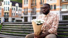Assento africano do homem só no banco da cidade, guardando o ramalhete da flor, falhado data imagens de stock royalty free