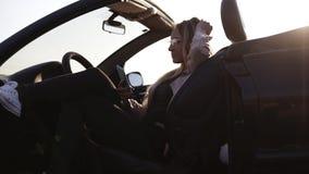 Assento atrativo novo da menina, relaxando em seu carro desportivo preto e guardando o telefone celular Está vestindo óculos de s video estoque