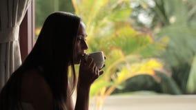 Assento atrativo novo da mulher, olhando à janela e ao chá bebendo filme