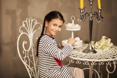 Assento bonito da menina e ir comer bolos Imagens de Stock
