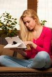 Assento confortável da mulher no sofá e no tablet pc da utilização Imagens de Stock