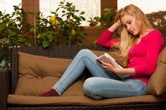 Assento confortável da mulher no sofá e no tablet pc da utilização Imagem de Stock Royalty Free