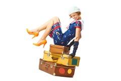 Assento da jovem mulher em malas de viagem do vintage Imagens de Stock Royalty Free