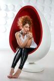 Assento da jovem mulher na cadeira do ovo Fotografia de Stock
