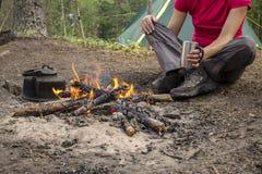 Assento da menina ao acampar perto do fogo caloroso e do chá quente da bebida imagens de stock royalty free