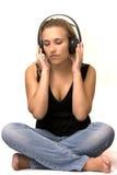 Assento da menina para sentir o som através dos auscultadores Fotos de Stock Royalty Free