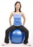 Assento da mulher na bola dos pilates Fotografia de Stock