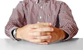 Assento das mãos dos homens oposto na tabela Fotos de Stock
