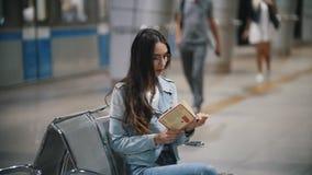 Assento de espera com um livro em um banco no metro, movimento lento da menina vídeos de arquivo