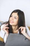 Assento de relaxamento da mulher confortável na câmera de vista feliz de sorriso da cadeira de sala de estar do sofá Retrato de u Imagens de Stock Royalty Free