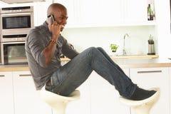 Assento de relaxamento do homem na cozinha que fala no telefone Foto de Stock Royalty Free