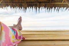 Assento de relaxamento dos povos na cabana no mar Foto de Stock Royalty Free