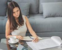 Assento de sorriso da menina asiática bonita trabalhando em casa o projeto com fotos de stock