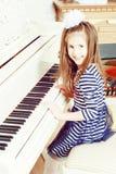 Assento de sorriso da menina atrás das chaves de um grande piano branco Fotografia de Stock