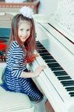 Assento de sorriso da menina atrás das chaves de um grande piano branco Fotografia de Stock Royalty Free
