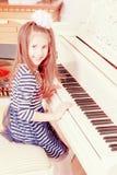 Assento de sorriso da menina atrás das chaves de um grande piano branco Imagem de Stock