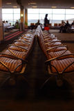 Assento do aeroporto com os viajantes no fundo Imagens de Stock Royalty Free