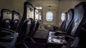 Assento e janelas do avião dentro de um avião Janela do passageiro do avião das nuvens fotos de stock royalty free