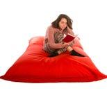 Assento e leitura bonitos novos da mulher um livro no quadrado vermelho dado forma Fotos de Stock Royalty Free
