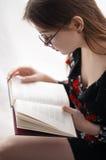 Assento e leitura da menina Fotos de Stock Royalty Free