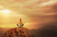 Assento e meditar da jovem mulher Imagens de Stock