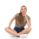Assento e pensamento de sorriso da mulher Fotos de Stock Royalty Free