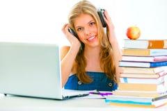 Assento em lições audio de escuta da menina da tabela Foto de Stock