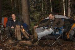 Assento em torno do fogo do acampamento fotografia de stock royalty free