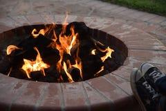 Assento em torno do poço do fogo do quintal em uma noite morna foto de stock
