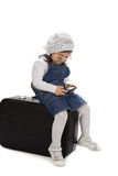 Assento em uma menina da mala de viagem que joga com telefone Imagens de Stock