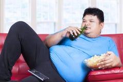 Assento excesso de peso do homem preguiçoso no sofá Fotografia de Stock Royalty Free