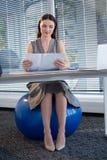 Assento executivo fêmea na bola do exercício ao ler originais na mesa imagens de stock royalty free