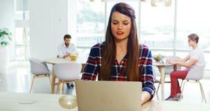 Assento executivo fêmea na mesa e no portátil da utilização vídeos de arquivo