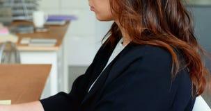 Assento executivo fêmea na mesa e no portátil da utilização video estoque